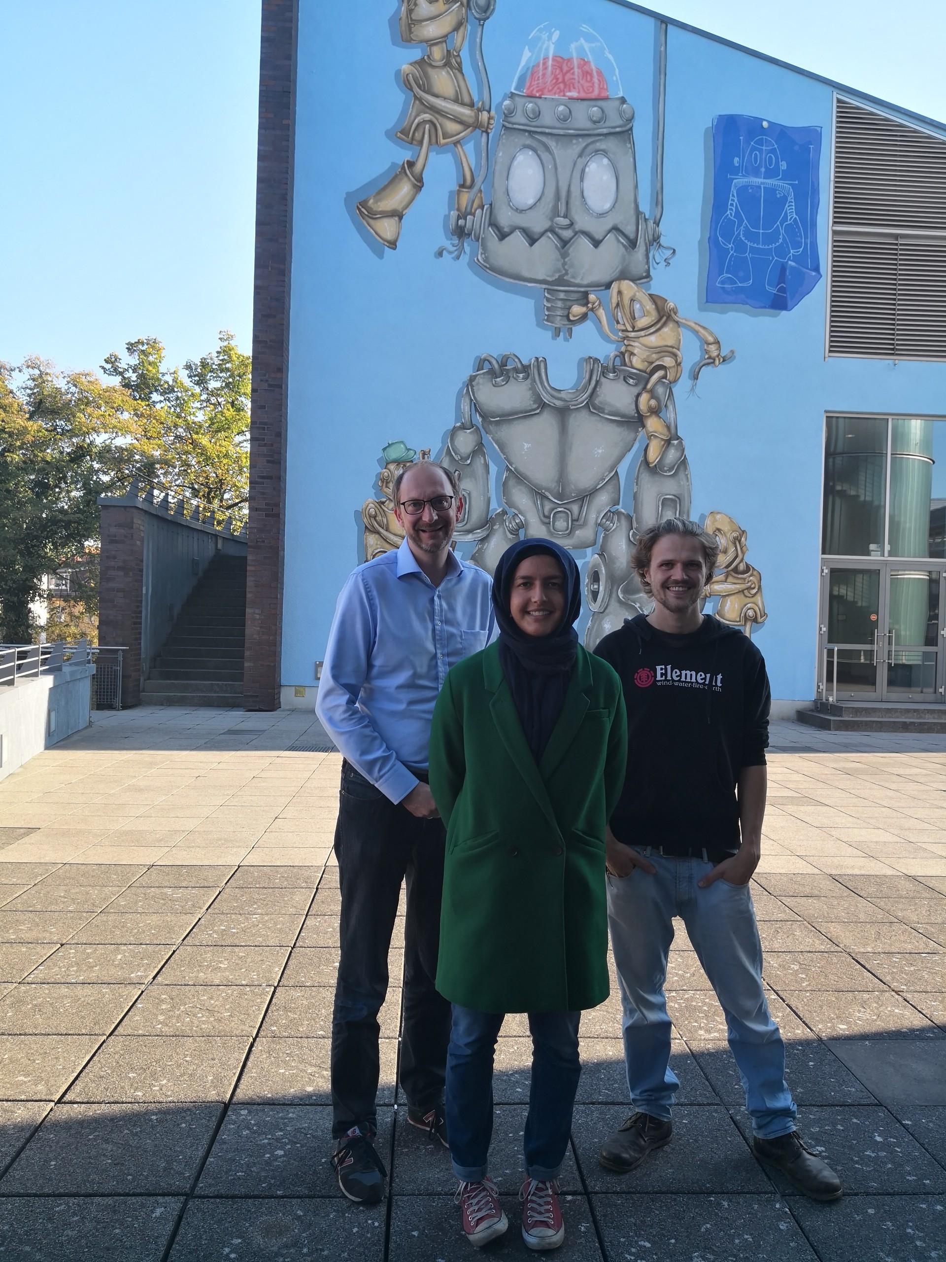 TUHH -Dr. Ralf Grote Labiba Ahmed und Konstantin Lafermann vor einem Teil des Kunstwerkes.