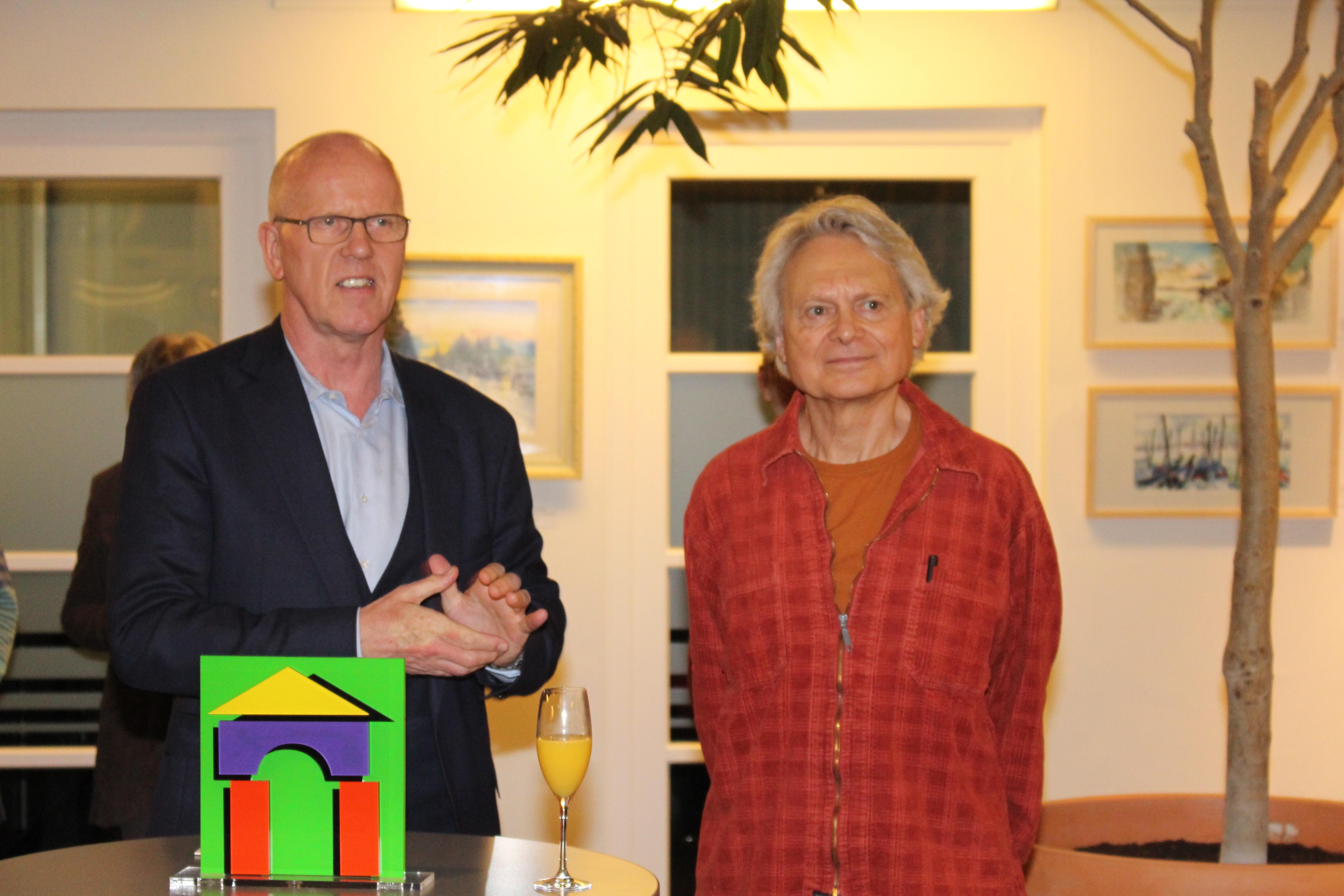 pm -Joachim Bode (links) begrüßt den Künstler Peter Schneider im Atrium der Genossenschaft
