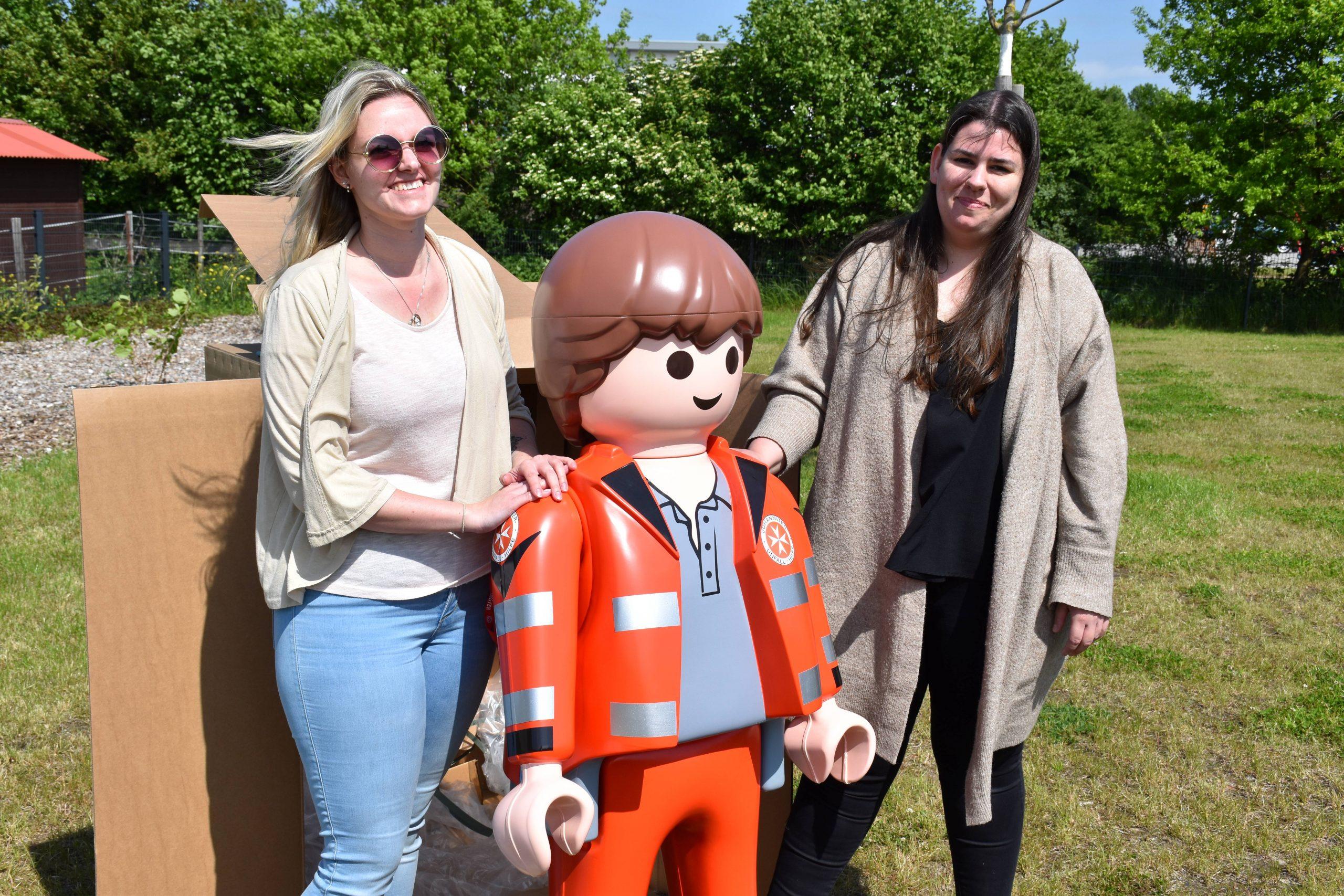 Johanniter -Vanessa Frerichs (l.) und Stephanie Bröker packten die Playmobil-Figur im Garten der Krümelkiste aus